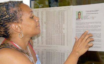 A woman reads the names of the candidates for a municipality in Havana.