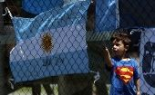 A boy stands next to an Argentine national flag with a message in support of the 44 crew members of the missing ARA San Juan submarine.