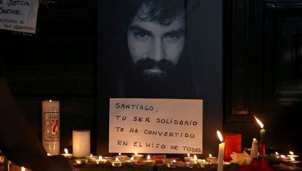 A man lights candles next to a portrait of Santiago Maldonado, whose body was found 78 days after he disappeared.