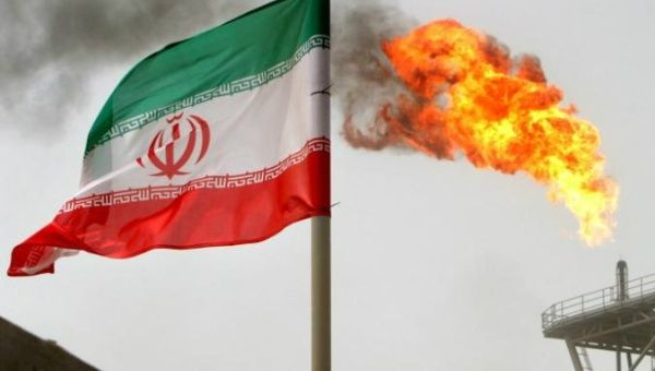 A gas flare on an oil production platform is seen alongside an Iranian flag in the Gulf July 25, 2005.
