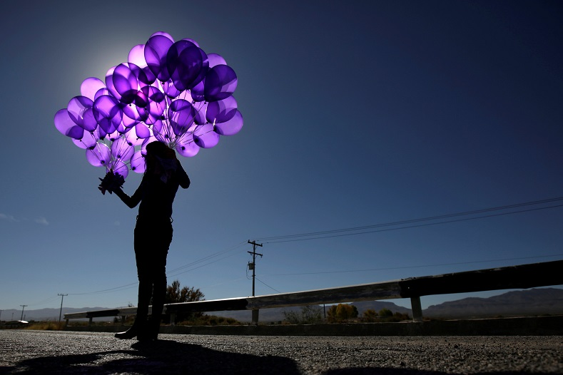 An activist holds purple balloons at El Navajo creek, where the bodies of several women were found, during a ceremony to mark the International Day for the Elimination of Violence Against Women on the outskirts of Ciudad Juarez, Mexico.