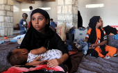 A Yemeni girl holds a baby in a temporary shelter after fleeing violence in Yemen, at the port town Bosasso in Somalia