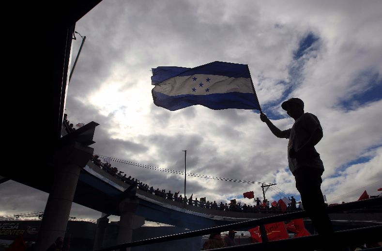 A supporter of Nasralla raises the Honduran flag as election results are awaited.