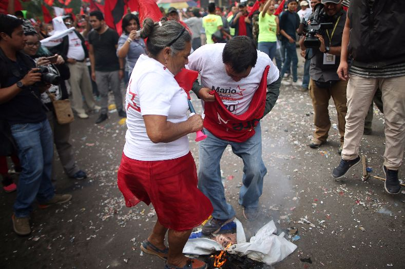 Supporters of Nasralla trample on a picture of incumbent candidate Juan Orlando Hernandez.