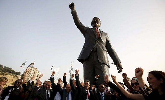 People seen cheering in Nelson Mandela Square in Ramallah before a statue of the late African leader.