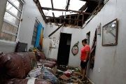 A woman stands in her home in Puerto Rico after Hurricane Maria.