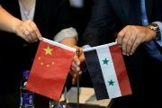 Chinese and Syrian businessmen shake hands behind their national flags during a meeting to discuss reconstruction projects in Syria, Beijing, China May 8, 2017.