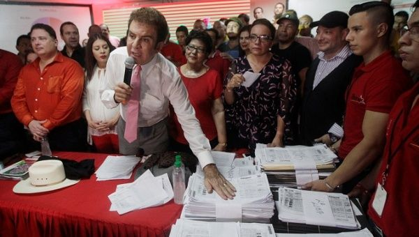 Salvador Nasralla, presidential candidate for the Opposition Alliance Against the Dictatorship, shows the tallies of ballot counting during a news conference in Tegucigalpa.