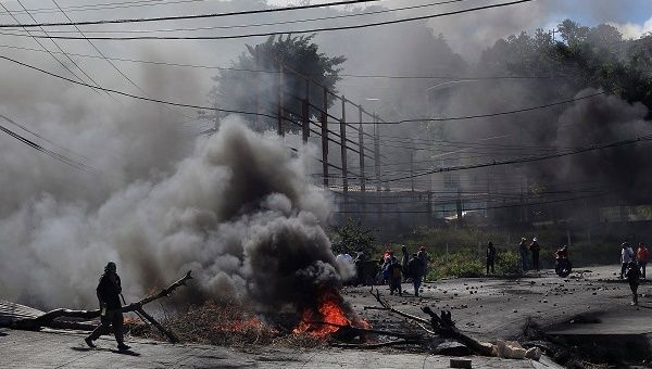 An opposition supporter passes a burning barricade during a protest caused by the delayed vote count for the presidential election in Honduras.