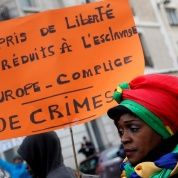 "A woman holds a placard with the message ""Loving Freedom, reduced to slavery. Europe is an accomplice to crimes "" as she attends a protest against slavery in Libya outside the Lybian Embassy in Paris, France, November 24, 2017"