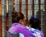 A woman carries her son while talking to her husband across the fence separating Mexico and U.S, as photographed from Tijuana, Mexico.