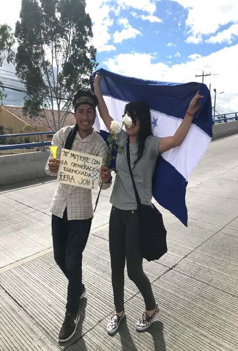 """Unos jóvenes caminaron con la bandera de Honduras, rosas blancas y un cartel que decía: """"Te metiste con la juventud equivocada, fuera JOH""""."""