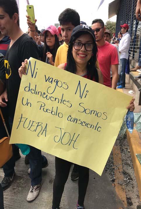 """""""Ni vagos ni delincuentes, somos un pueblo consciente, Fuera JOH"""", se leía en otra pancarta."""