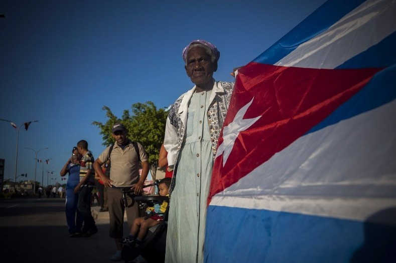 A woman carries the Cuban flag in procession.