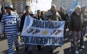 "Argentines march with banner thats reads, ""Malvinas belongs to Argentina."""