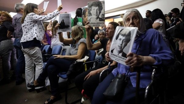People hold portraits of those who disappeared during Argentina