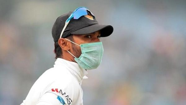 A Sri Lankan player wears a face mask to protect himself from India