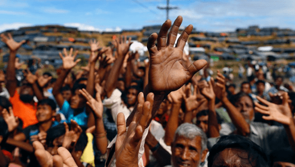 Rohingya refugees stretch their hands to receive aid distributed by local organisations at Balukhali makeshift refugee camp in Cox