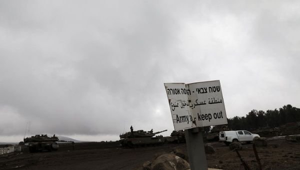 Israeli soldiers stand atop tanks in the Israeli-occupied Golan Heights.