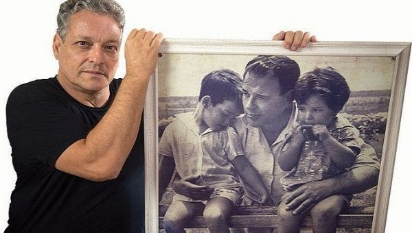 João Vicente Goulart holds a portrait of himself, his father, João Goulart, and his sister, Denize.