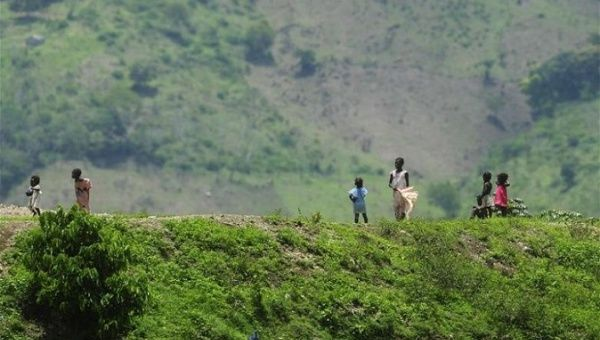 Haitian children stand on a ridge alongside the road that divides Hispaniola island into the Dominican Republic and Haiti to the west.