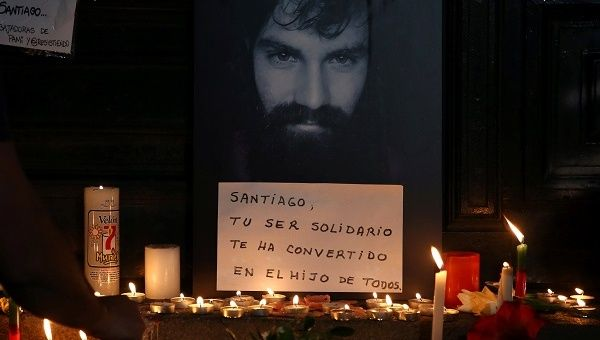 A man lights candles next to a portrait of Santiago Maldonado, who went missing after security forces clashed with indigenous activists in Patagonia on August 1.