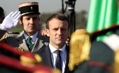 French President Emmanuel Macron reviews troops at Algiers Airport following his arrival in Algeria, December 6.