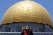 A Palestinian woman prays in front of the Dome of the Rock in Jerusalem's Old City.