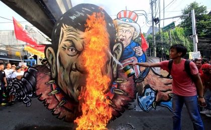 An activist pours gasoline as an effigy of President Rodrigo Duterte and U.S. President Donald Trump burns during a protest action against Duterte