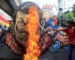 An activist pours gasoline as an effigy of President Rodrigo Duterte and U.S. President Donald Trump burns during a protest action against Duterte's plan to set up a Revolutionary Government, along a street in metro Manila, Philippines November 30, 2017.