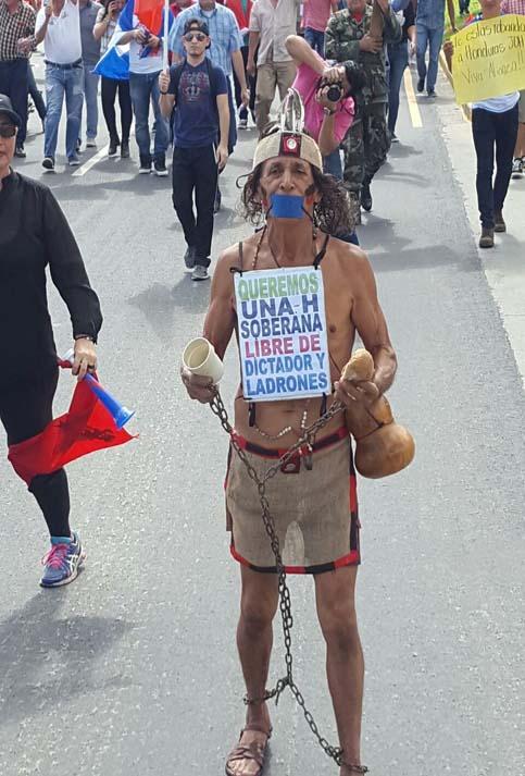 """Unos de los asistentes fue vestido de indígena con una consigna que decía """"Queremos una Honduras soberana libre de dictadores y ladrones""""."""