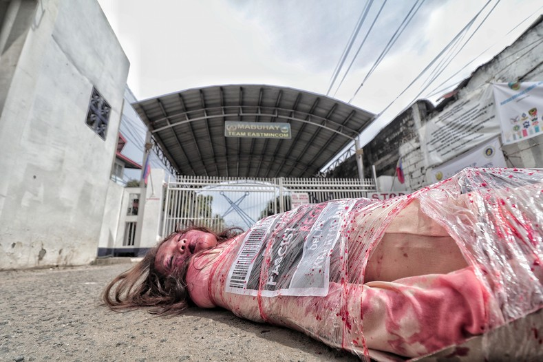 "Protesters held a mock die-in, stripped naked and covered in ""blood"" while wrapped in cellophane and ""dumped"" in front of AFP headquarters."