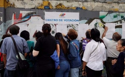 People check a list at a polling station during a nationwide election for new mayors, in Caracas, Venezuela December 10, 2017.
