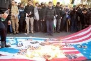 Iranians burning photos on a flag at a rally protesting Israel.