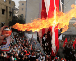 Protesters set a U.S flag on fire near the U.S. Embassy in Awkar north of Beirut, Lebanon, Dec. 10,2017.