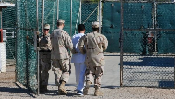 U.S. guards escort a detainee through Camp Delta at Guantanamo Bay naval base in this 2008 file photo from the U.S. Department of Defense.