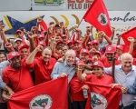 Lula (center) shows support for the Landless Workers' Movement, MST, on his caravan bus tour.