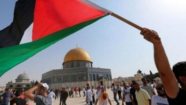 A demonstrator holds a Palestinian flag in front of the al-Aqsa Mosque.