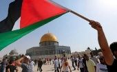 A demonstrator hold a Palestinian flag in front of the al-Aqsa Mosque.