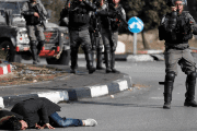 A Palestinian man lies on the ground after being shot by Israeli forces.