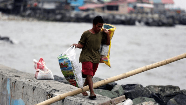 Filipino resident with his belongings at a coastal village in Cavite.