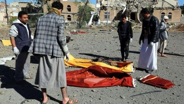 Yemenis collect the corpses of people killed in Saudi airstrike in Sana