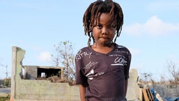 TJ Hickson, de 5 años, se encuentra al aire libre cerca de un edificio de ladrillo parcialmente destruido, en South Hill District, en la isla de Anguila, que fue duramente golpeado durante el huracán Irma.