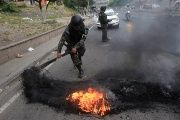 A military police removes a burning tire from a barricade settled by opposition supporters during a protest, in Tegucigalpa, Honduras December 18, 2017.