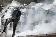 A Honduran soldier kicks a tear gas canister during a clash with protesters.