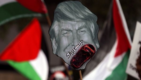 Pro-Palestine protesters hold a placard of U.S. President Donald Trump as they march towards the U.S. Embassy in Kuala Lumpur, Malaysia Dec. 15, 2017.