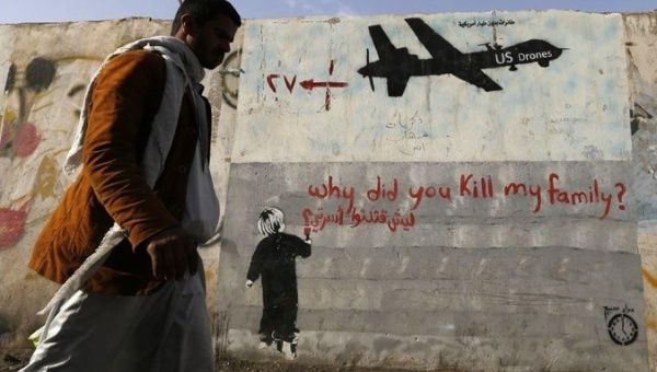 A man walks past a graffiti, denouncing strikes by U.S. drones in Yemen, painted on a wall in Sanaa Nov. 13, 2014.