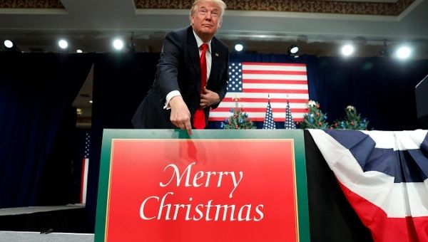 "U.S. President Trump points to a large ""Merry Christmas"" card on the stage as he arrives to deliver remarks on tax reform in Missouri, U.S. Nov. 29, 2017."