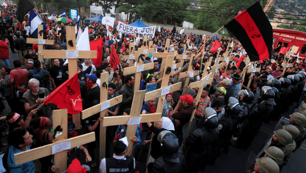 Honduran protesters hold aloft wooden crosses in front of security forces guarding the U.S. Embassy.