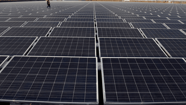 A worker examines a vast field of solar panels in China, in a scene that may some day be extended across Cuba.